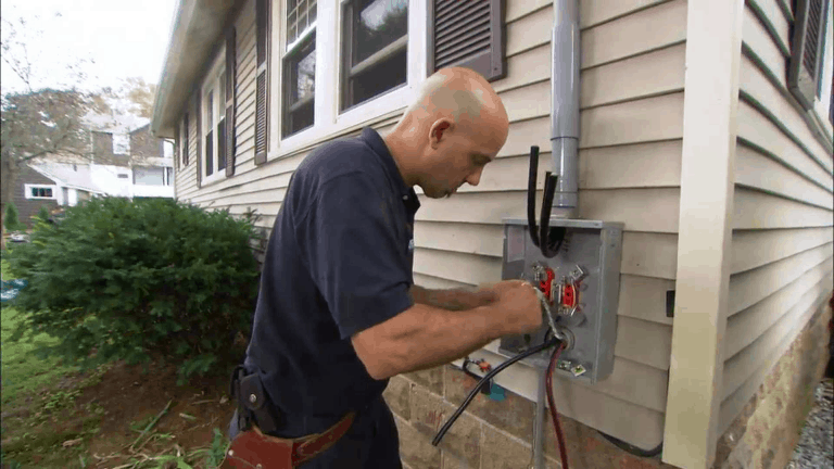 electrician installing electric meter box on house exterior