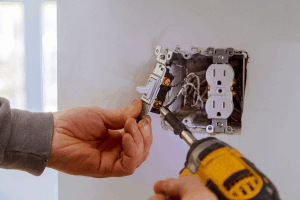 electrician terminating wires to light switch with drill