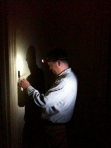 electrician wearing head lamp working on light switch